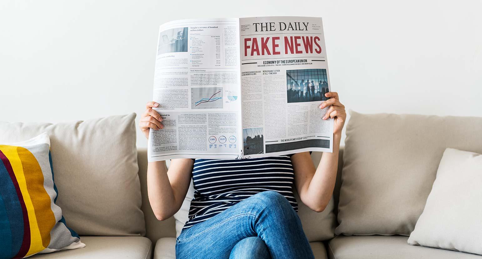 Woman reading newspaper with fake news headline