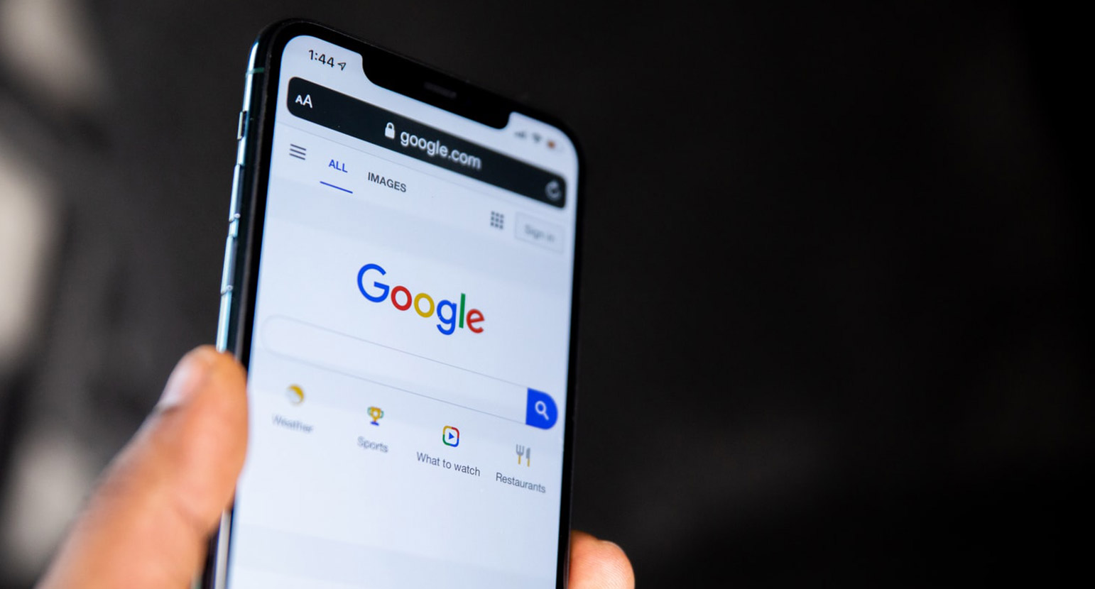 Hand holding up phone with Google Search on the screen.