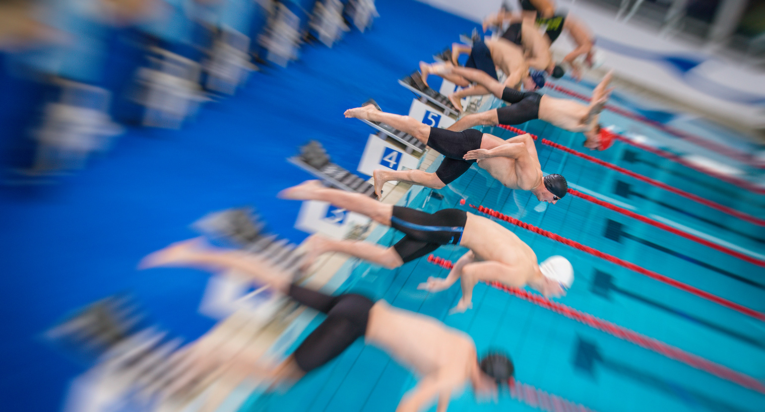 Swimmers jumping off starting block