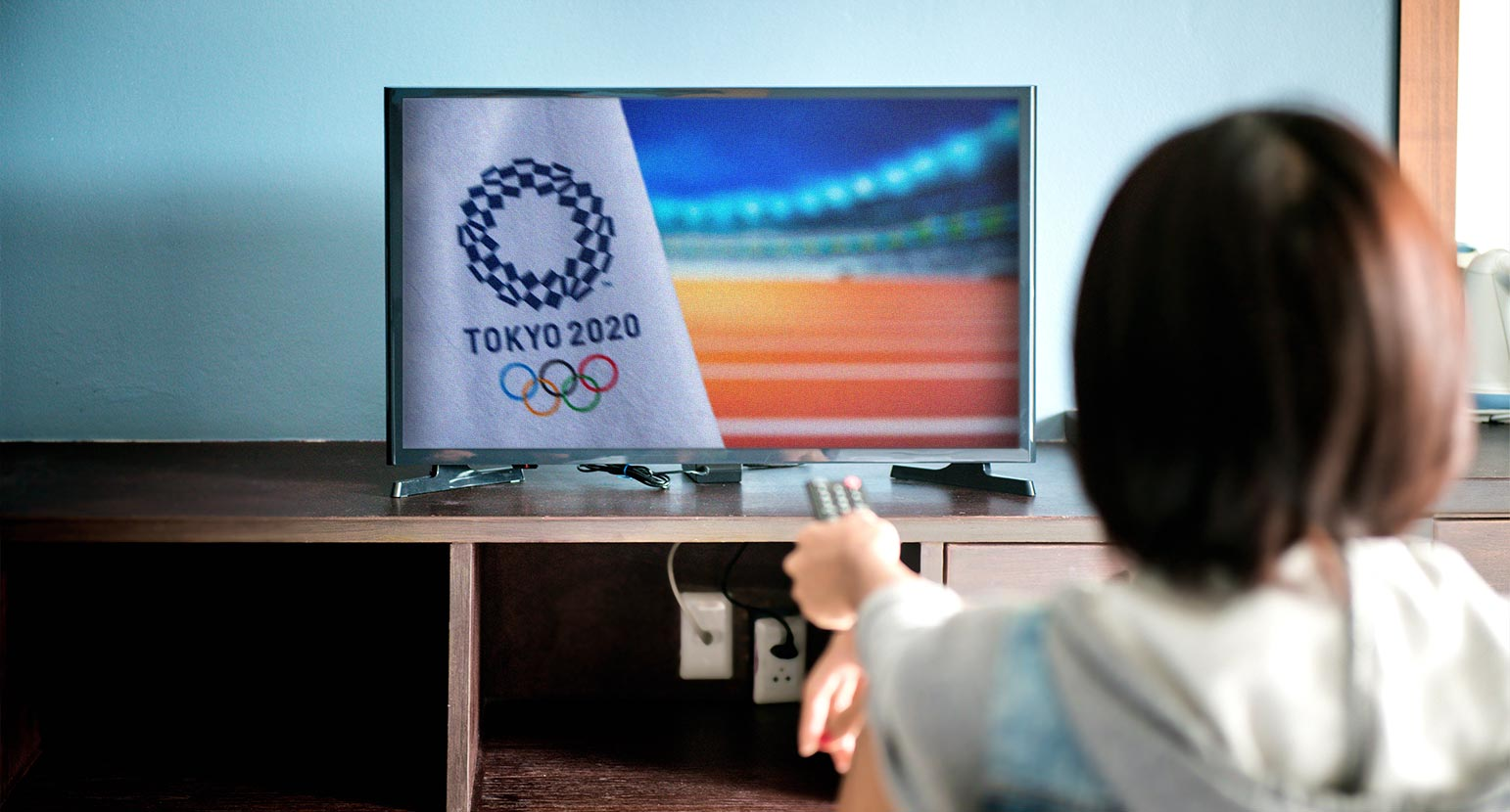 Woman watches Tokyo 2020 Olympics on TV